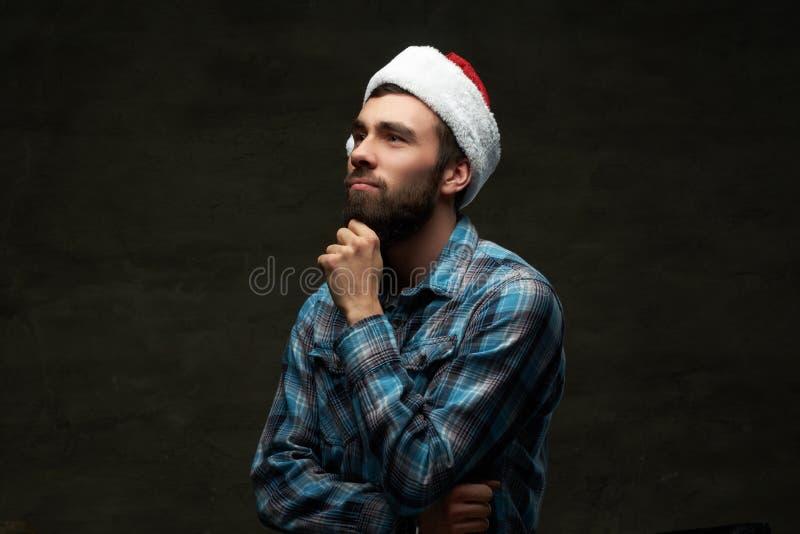 Homem farpado pensativo que veste uma camisa e um chapéu quadriculados de Santa, isolados em um fundo escuro fotografia de stock