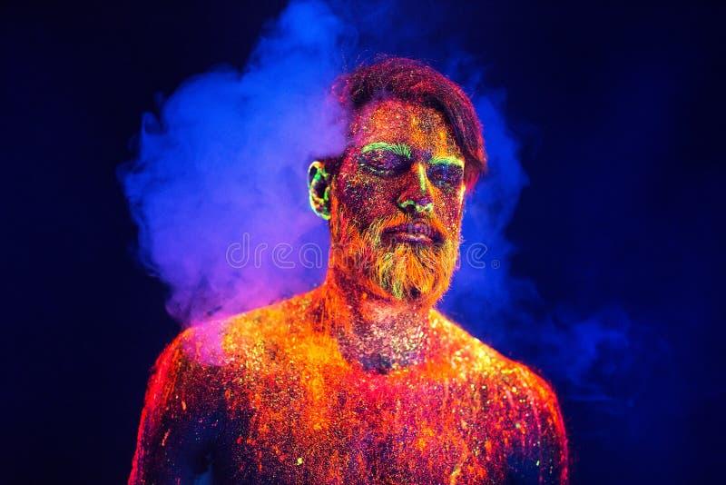 Homem farpado pintado no pó fluorescente em um fundo do fumo foto de stock royalty free