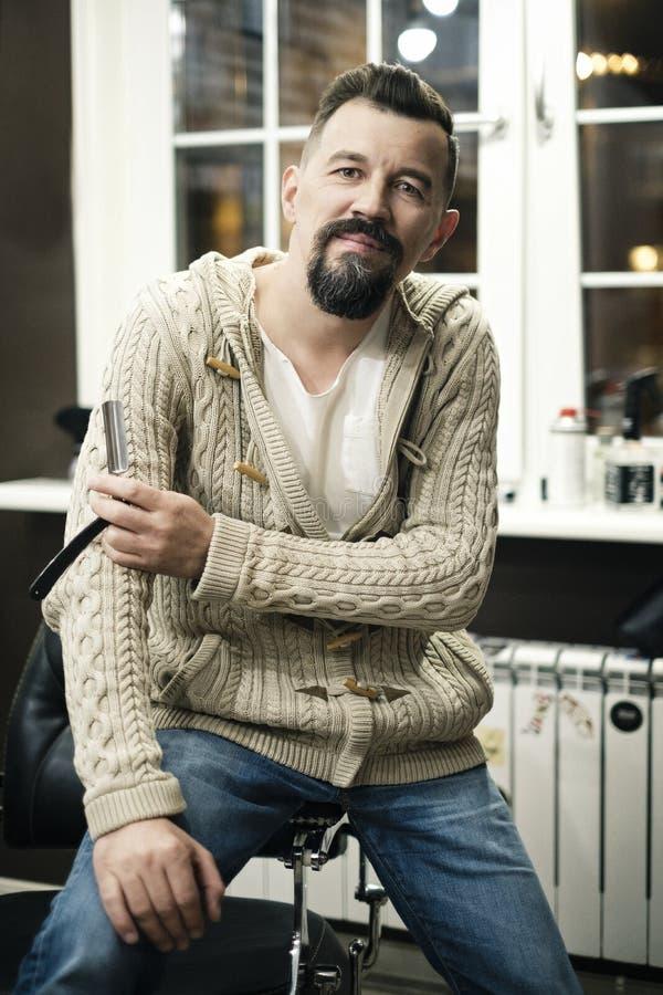 Homem farpado que barbeia na barbearia com lâmina de lâmina Cabeleireiro profissional que guarda uma lâmina em sua mão imagem de stock royalty free
