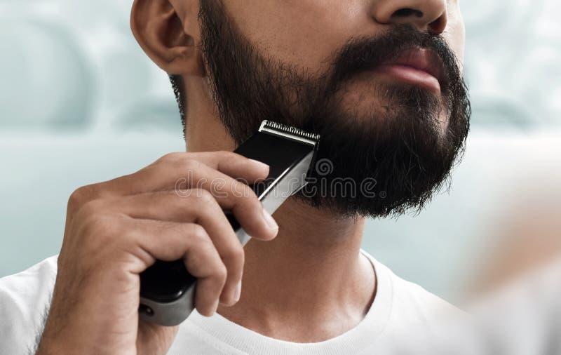 Homem farpado que barbeia sua barba fotografia de stock royalty free
