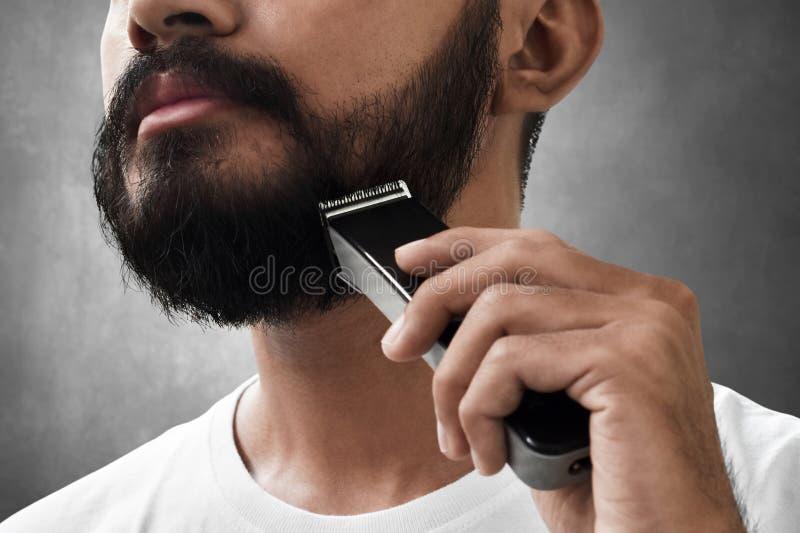 Homem farpado que barbeia sua barba fotos de stock royalty free