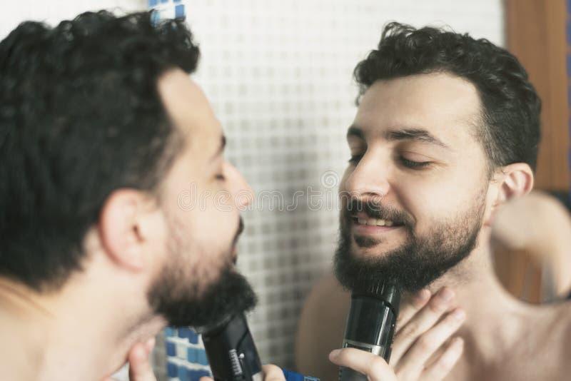 Homem farpado que barbeia sua barba com a máquina de rapagem da lâmina fotos de stock