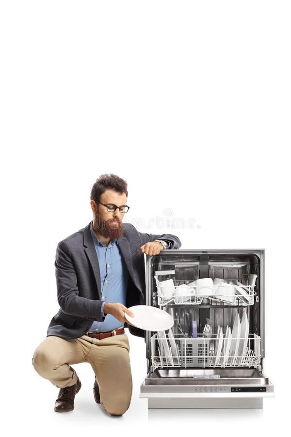 Homem farpado que carrega uma máquina de lavar louça imagem de stock royalty free