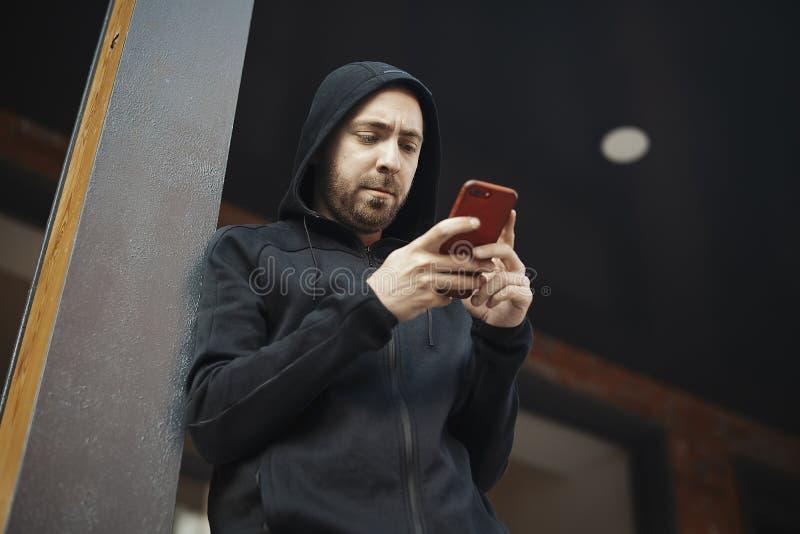 Homem farpado que está ao lado do cargo concreto e que olha fixamente na tela foto de stock royalty free