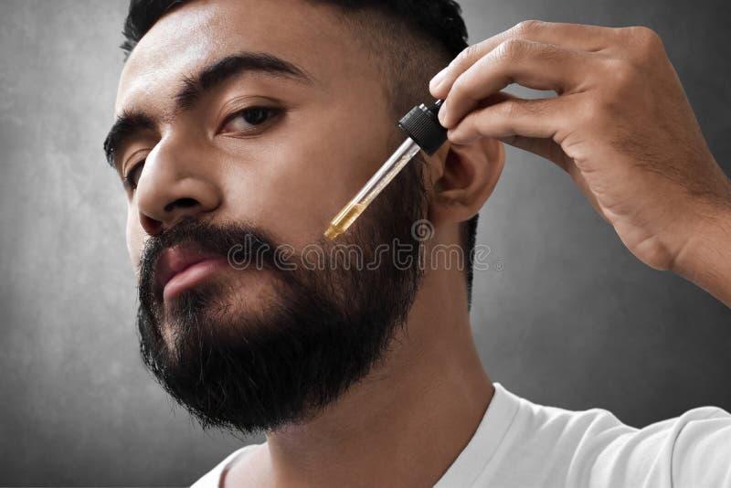 Homem farpado que guarda o pippete com óleo da barba imagens de stock