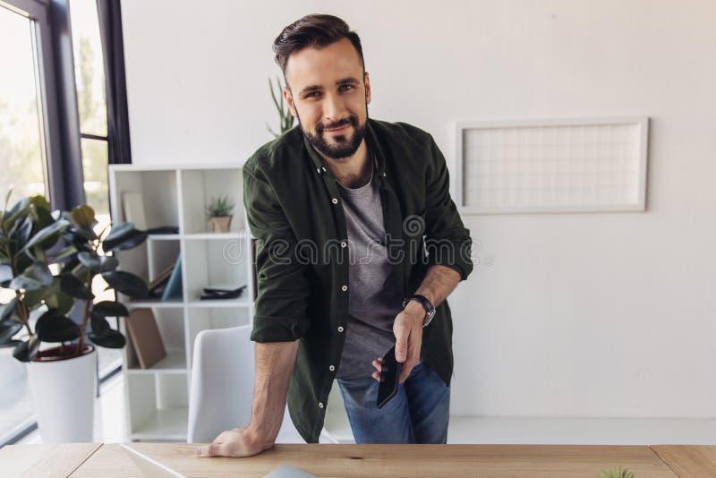 Homem farpado que guarda o smartphone e que sorri na câmera no escritório imagens de stock