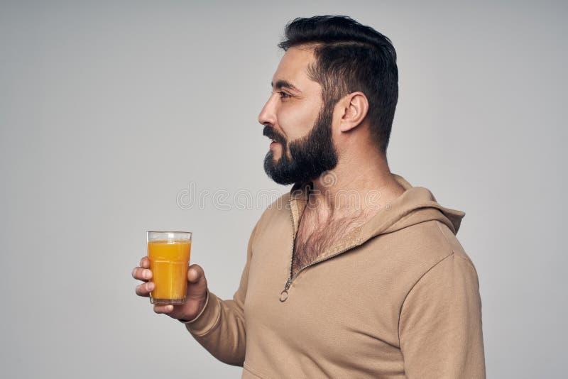 Homem farpado que guarda um vidro do suco de laranja imagem de stock