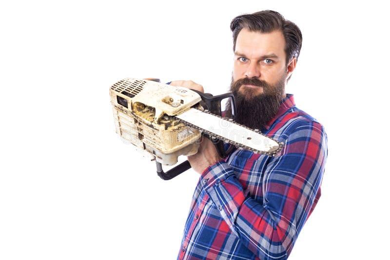Homem farpado que mantém uma serra de cadeia isolada em um fundo branco fotos de stock royalty free