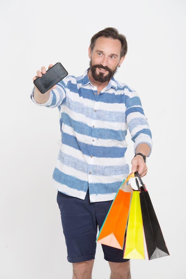 Homem farpado que mostra seu smartphone ao estar com sacos de papel foto de stock
