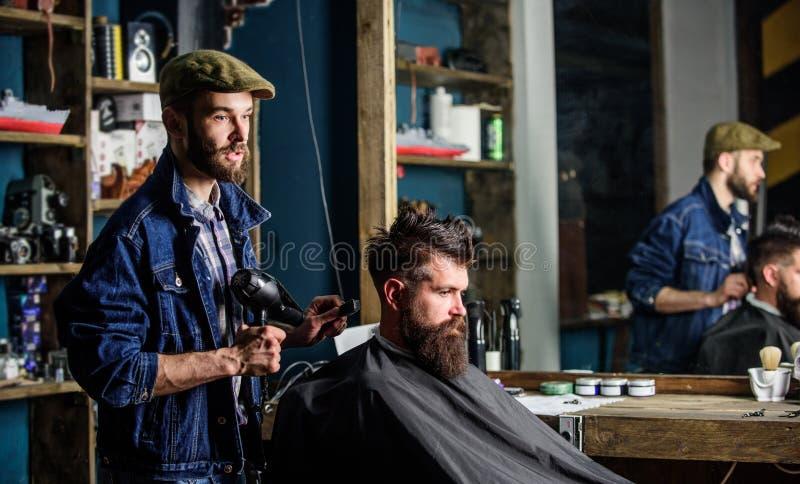 Homem farpado que obtém preparado no cabeleireiro com secador de cabelo ao sentar-se na cadeira no barbeiro Conceito do moderno foto de stock