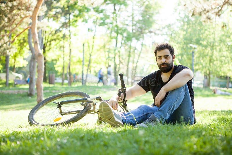 Homem farpado que olha longe da câmera com sua bicicleta ao lado dele foto de stock royalty free