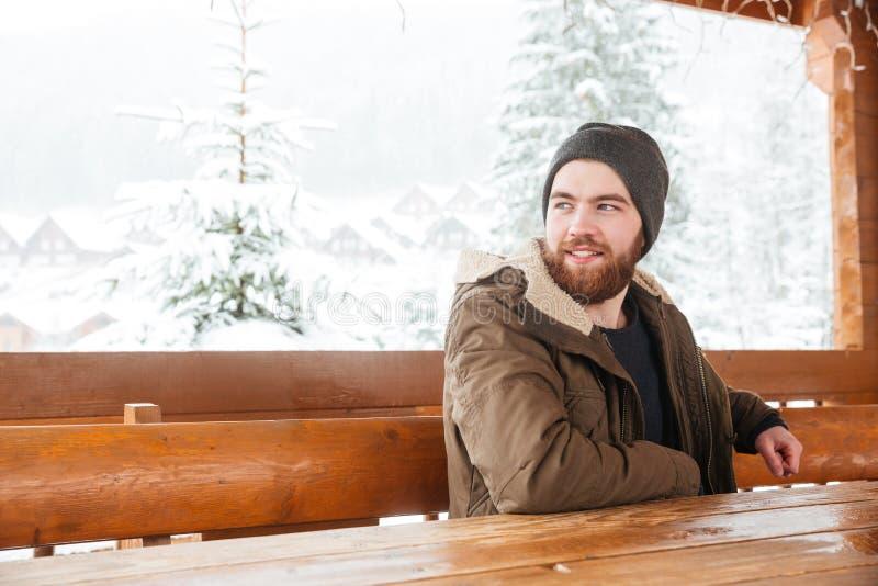 Homem farpado que senta-se e que sorri no inverno fora fotos de stock