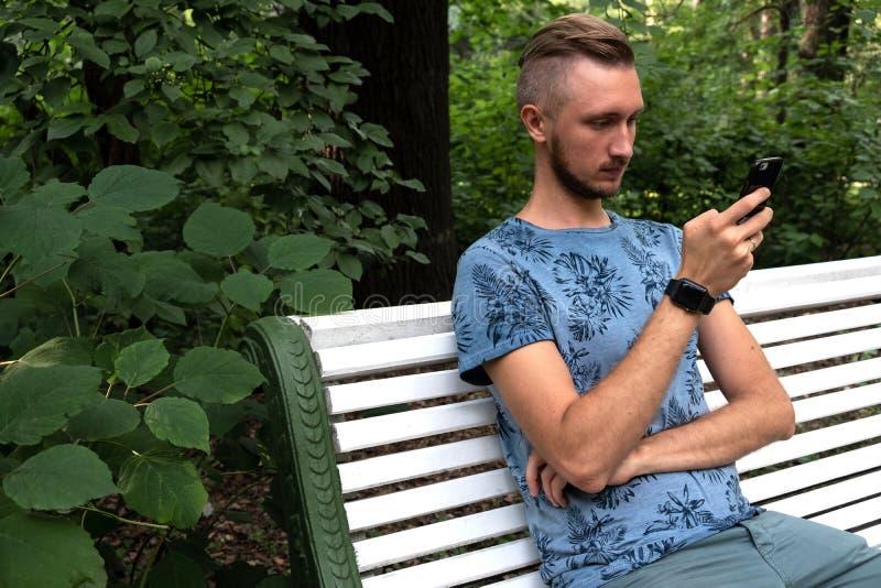 Homem farpado que senta-se no banco de parque com telefone celular, relógio esperto vestindo, fundo do jardim do verde do verão H fotos de stock royalty free