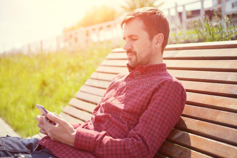 Homem farpado que senta-se no banco no parque com o telefone nas mãos fotos de stock