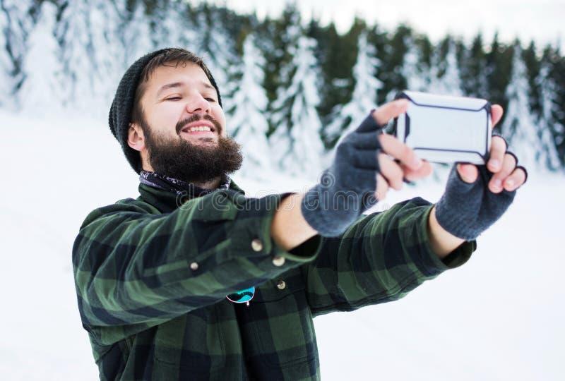 Homem farpado que toma o selfie na montanha nevado imagem de stock royalty free