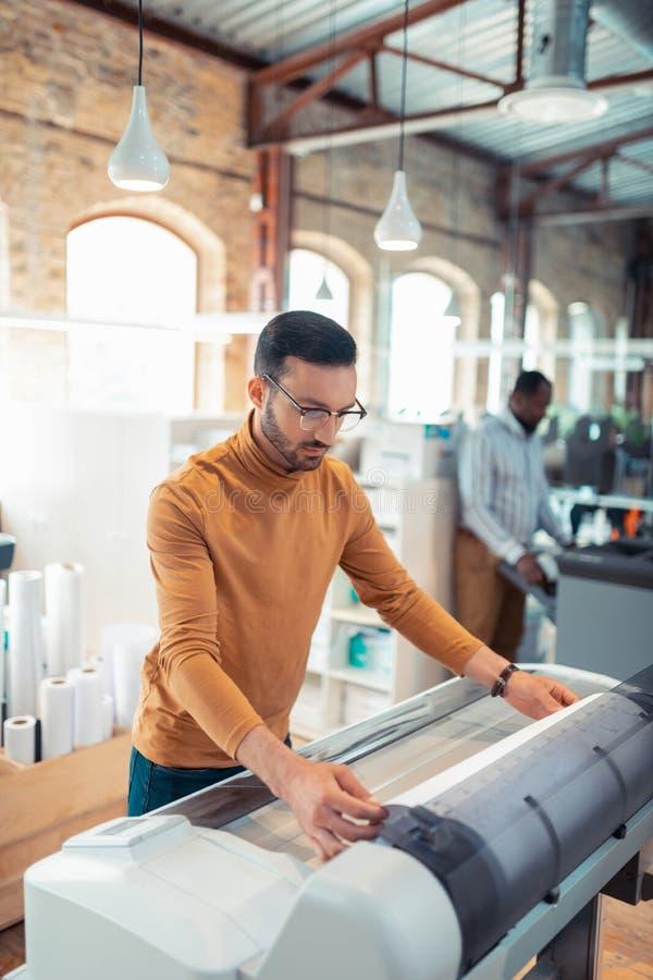 Homem farpado que usa a impressora grande ao imprimir cartazes fotografia de stock