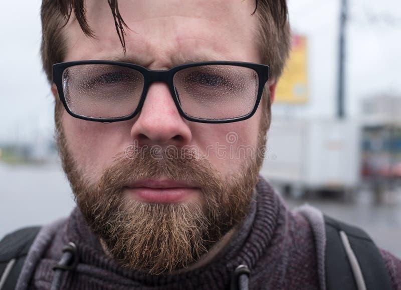 Homem farpado sério, descontentado nos vidros misted devido à umidade forte e chuva chuviscando foto de stock