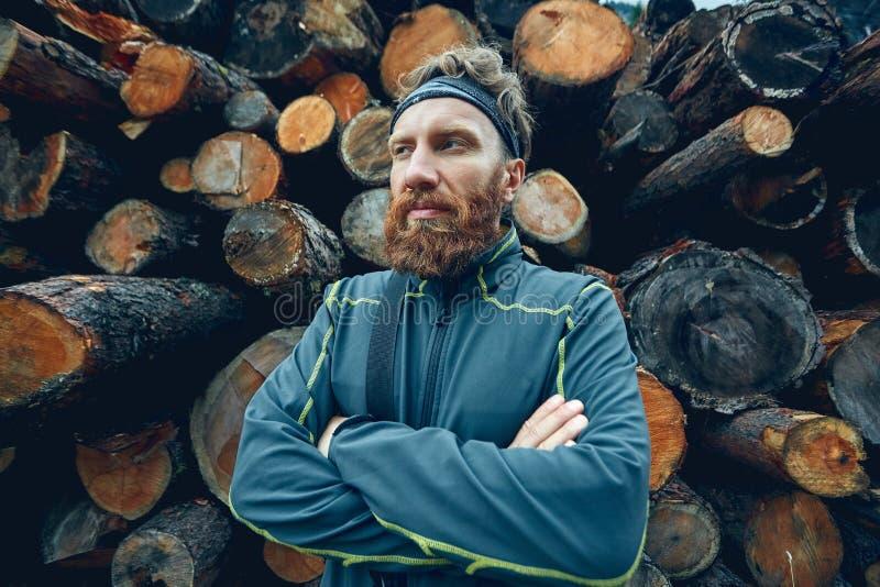 Homem farpado severo entre uma pilha dos logs imagens de stock