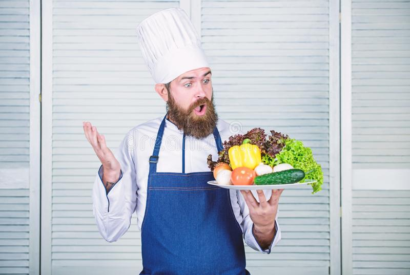 Homem farpado surpreendido receita do cozinheiro chefe Culin?ria culin?ria vitamina Salada do vegetariano com legumes frescos Die fotos de stock royalty free