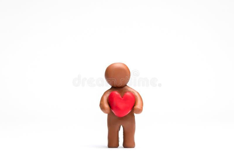 Homem feito do plasticine que guarda um coração no fundo branco, alinhado no centro imagem de stock