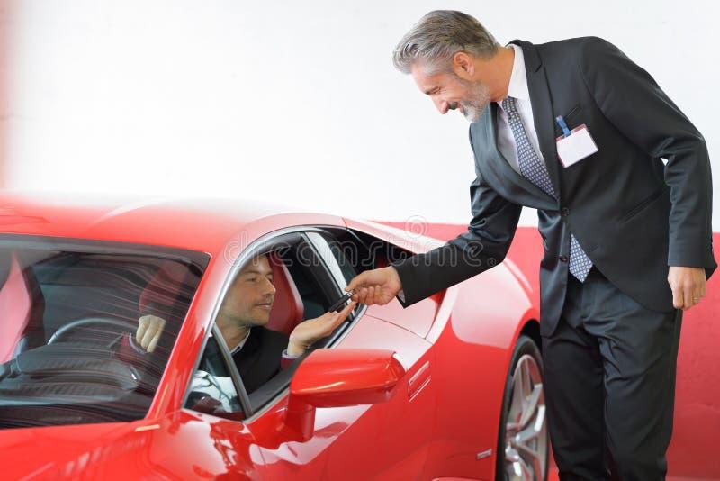 Homem feliz ao tentar o carro novo fotografia de stock royalty free