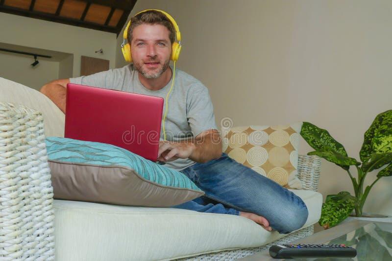 Homem feliz atrativo e considerável novo que senta em casa o sofá do sofá que trabalha com laptop e fones de ouvido usando o netb imagens de stock