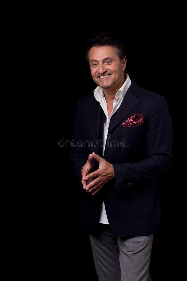 Homem feliz atrativo que sorri ao levantar para a foto fotografia de stock