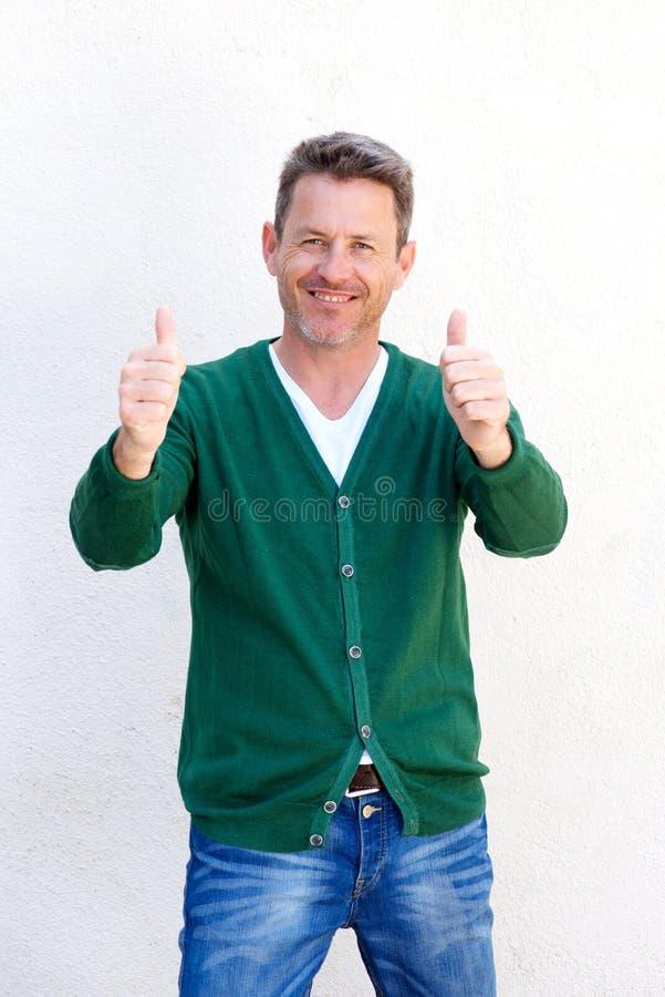 Homem feliz com ambos os polegares acima no fundo branco fotografia de stock royalty free