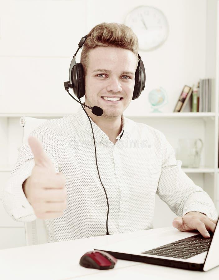 Homem feliz com auriculares e portátil imagem de stock royalty free