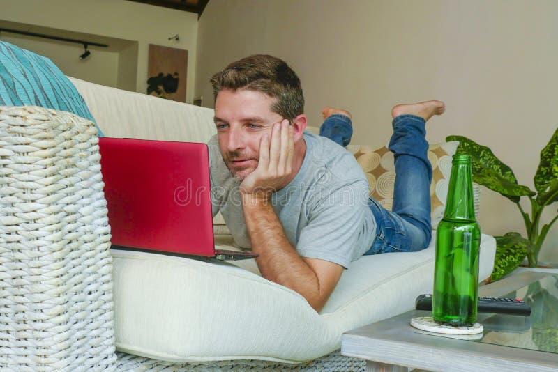 Homem feliz considerável novo que encontra-se em casa sofá do sofá que trabalha em linha com laptop usando confortável relaxado d fotografia de stock