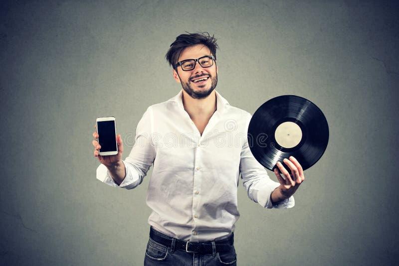 Homem feliz da barba do moderno que guarda o disco do registro de vinil e o smartphone moderno imagem de stock royalty free