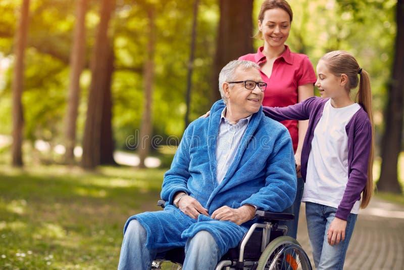 Homem feliz da cadeira de rodas com filha e neta fotografia de stock