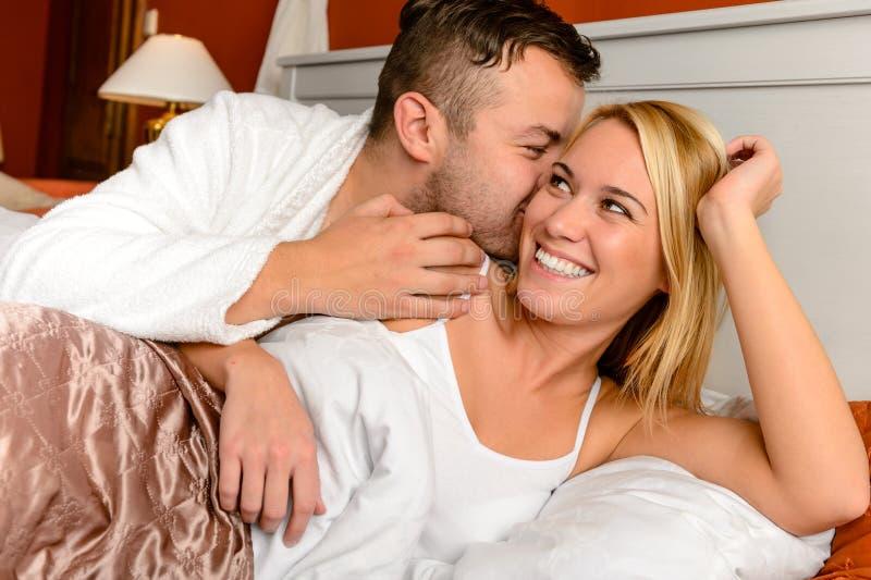 Homem feliz da cama dos pares que dá a mulher do beijo fotos de stock
