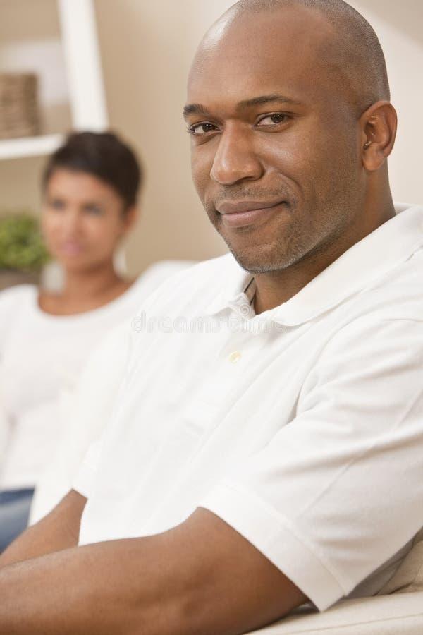 Homem feliz do americano africano que senta-se em casa imagens de stock royalty free