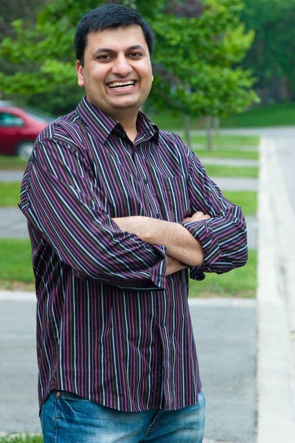 Homem feliz do indiano do leste ereto fora de sua casa imagem de stock