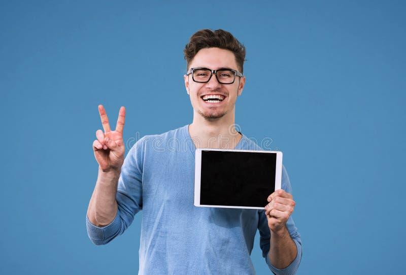 Homem feliz do moderno com o tablet pc que dá o sinal da vitória imagens de stock royalty free