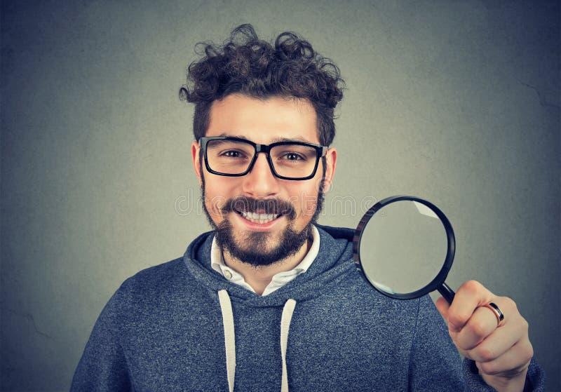 Homem feliz do moderno que levanta com vidro da lente de aumento fotografia de stock royalty free