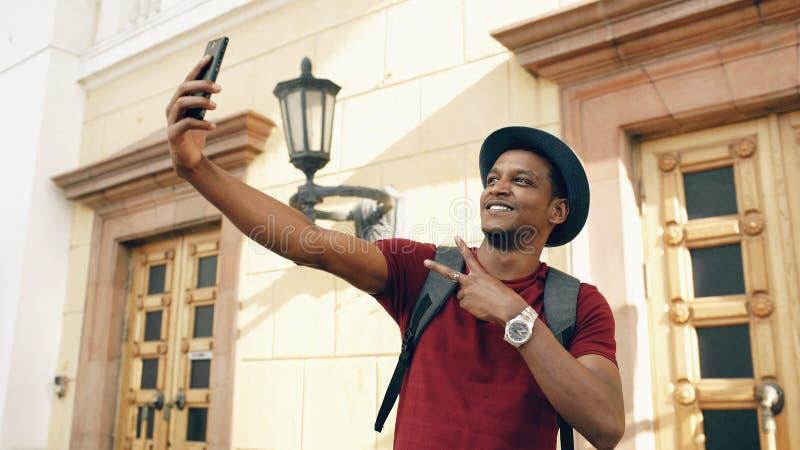 Homem feliz do turista da raça misturada que toma a foto do selfie em sua câmera do smartphone que está perto da construção famos fotos de stock