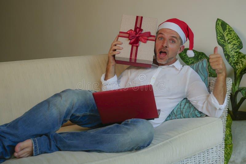 Homem feliz e atrativo no chapéu de Santa usando o cartão de crédito e no laptop que compra os presentes de Natal em linha que gu fotografia de stock