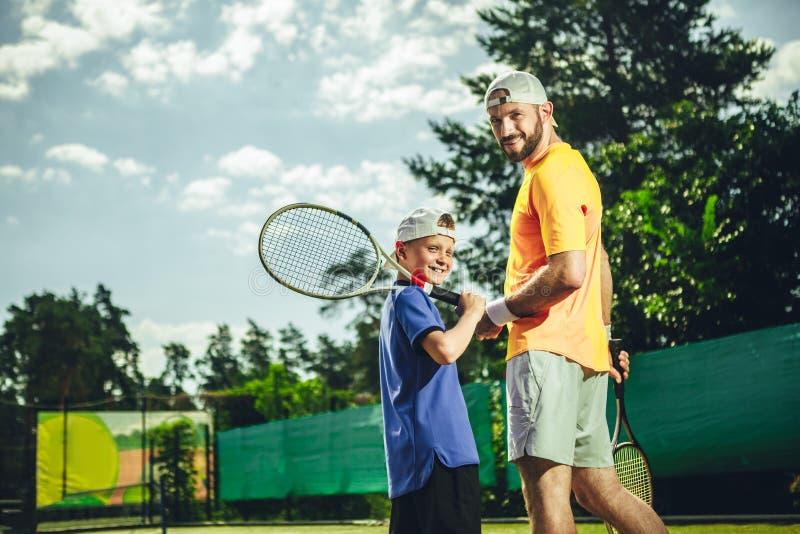 Homem feliz e menino que jogam o tênis fotografia de stock