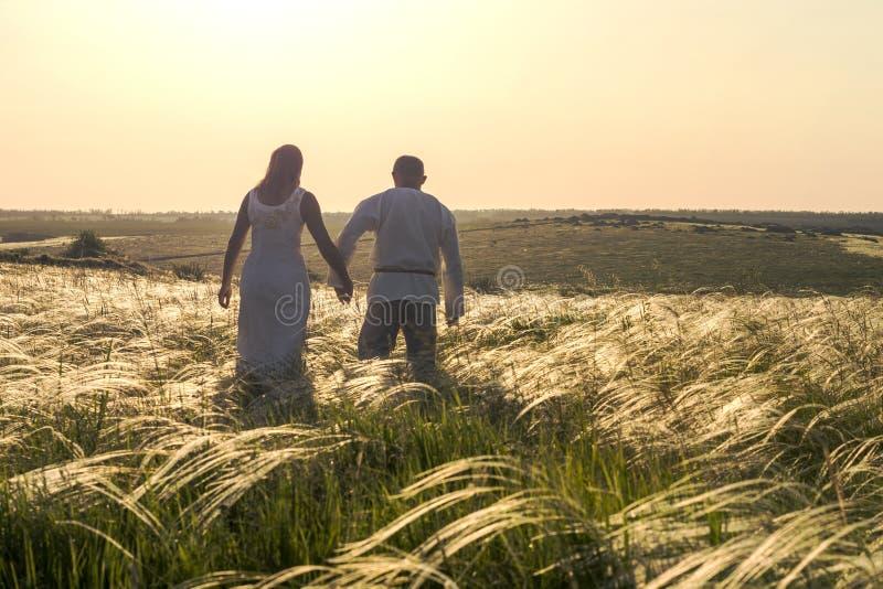 Homem feliz e mulher dos pares na roupa eslavo nacional que andam no campo no por do sol e que guardam as mãos Boa vinda a Rússia fotos de stock