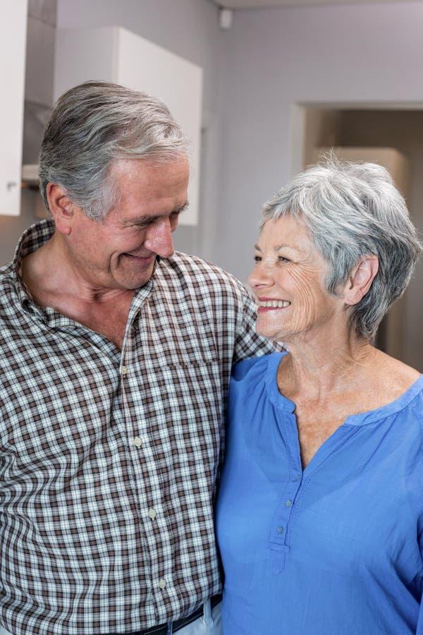 Homem feliz e mulher idosos que estão na cozinha foto de stock royalty free