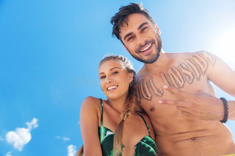 Homem feliz e mulher jovens que têm o divertimento na praia fotografia de stock