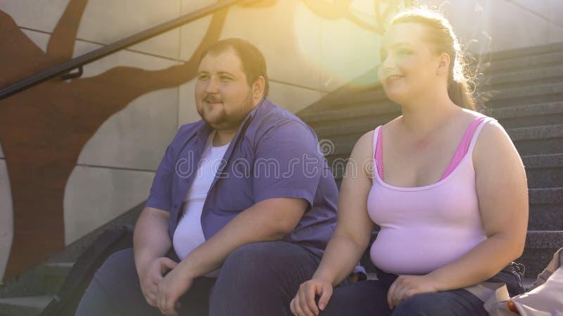 Homem feliz e mulher obesos que sentam-se em escadas e que sorriem, amizade, data imagens de stock