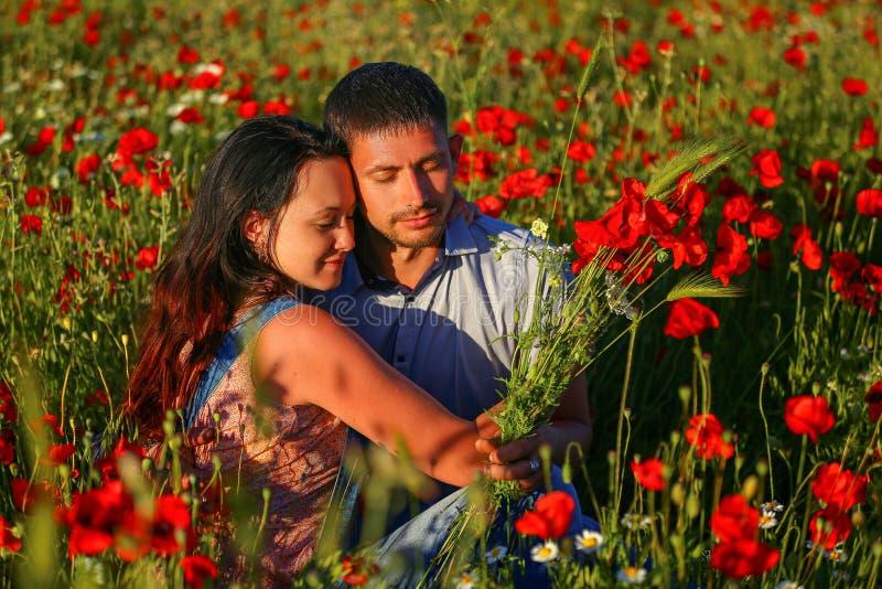 Homem feliz e mulher que abraçam em um campo das papoilas fotos de stock