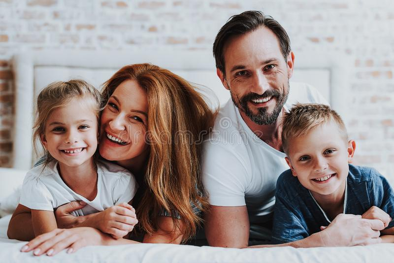 Homem feliz e mulher que colocam na cama com crianças imagens de stock royalty free