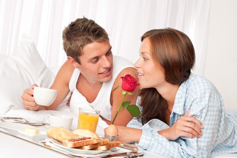 Homem feliz e mulher que comem o pequeno almoço foto de stock