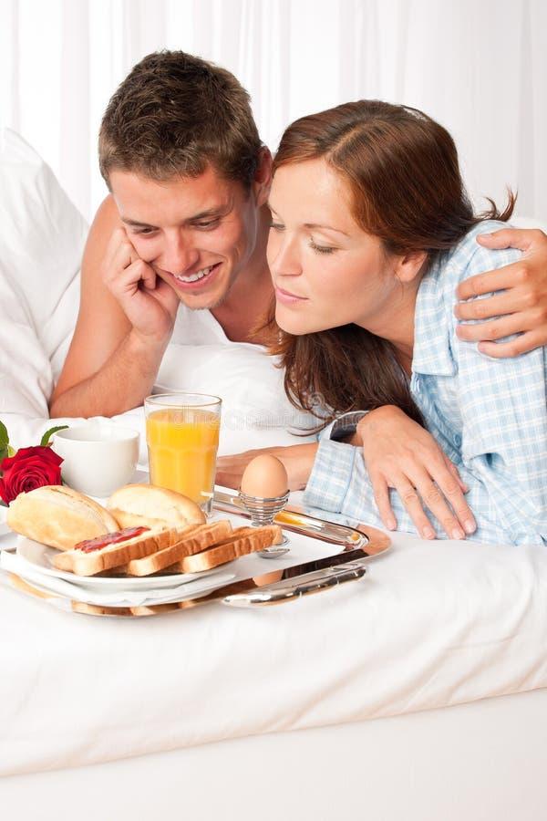 Homem feliz e mulher que comem o pequeno almoço imagem de stock royalty free