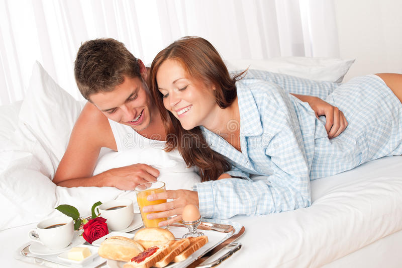 Homem feliz e mulher que comem o pequeno almoço na cama