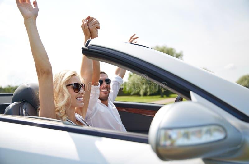 Homem feliz e mulher que conduzem no carro do cabriolet fotos de stock
